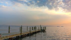 The wooden pier stretching into the sea cloudy sunset. The wooden pier stretching into the sea cloudy sunset royalty free stock photo