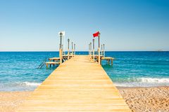 Wooden pier stretching into the sea, shot at dawn Royalty Free Stock Image