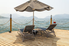 Wooden pier with sunbeds and parasols Stock Image