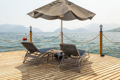Wooden pier with sunbeds and parasols Royalty Free Stock Photo