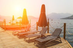 Wooden pier with sunbeds and parasols Royalty Free Stock Image