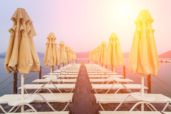 Wooden pier with sunbeds and parasols Stock Photos