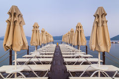 Wooden pier with sunbeds and parasols. On the background of sea and mountains royalty free stock image
