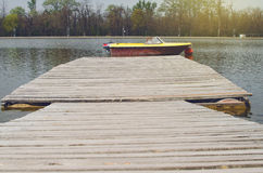 Wooden Pier In A Sunny Day With Parked Boat Royalty Free Stock Photo