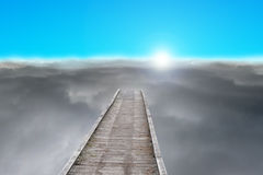 Wooden pier with sunrise, dark clouds and blue sky Royalty Free Stock Photos
