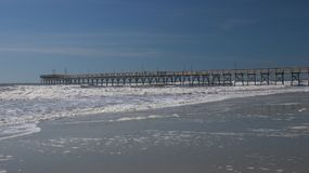 Wooden Pier at Sunset Beach, North Carolina. Sunset Beach Pier in the Atlantic Ocean on Sunset Beach, North Carolina Stock Images