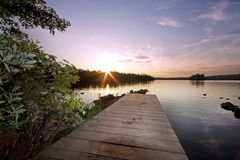Wooden pier at sunset by lake Stock Photos