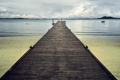 Wooden pier in Thai beach stock images