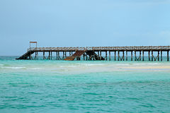 Wooden pier on tropical beach Royalty Free Stock Image