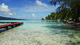 Wooden pier on tropical beach in french polynesia. Travel, seascape and nature concept - wooden pier and bungalows on tropical beach in french polynesia stock footage