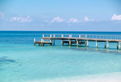Wooden Pier into Turquoise Caribbean Sea waters. Wooden pier with railing juts into the crystal blue waters of the Caribbean Sea on a sunny day with white cirrus stock images