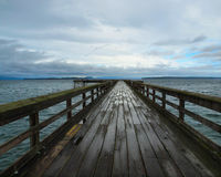 Wooden pier under stormy clouds after rain Stock Photos