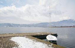 Boat under the snow at Vegoritis lake, Greece. royalty free stock images