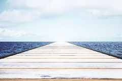 Wooden pier in the water with light sky Royalty Free Stock Photos