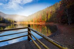 Wooden pierce fence on a lake in fog Stock Photos