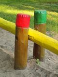 Wooden pillars in children playground. Dirty sand below colorful bars Royalty Free Stock Image