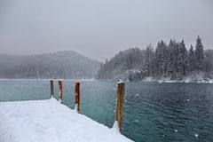 Wooden pillars guarding winter lake royalty free stock photography