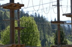 Wooden pillars and hanging ropes of a rope park on the background of green forest in the Carpathians. Ukraine. Wooden pillars and hanging ropes of a rope park on stock images
