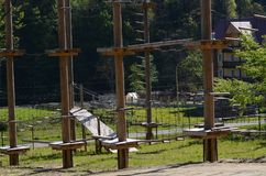 Wooden pillars and hanging ropes of a rope park on the background of green forest in the Carpathians. Ukraine stock photography