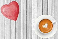 Wooden pink heart and coffee cup on white wooden texture close-u Royalty Free Stock Photo