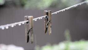 Wooden pins under rain. Wooden pins hanging on the rope under summer rain stock video