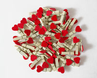 Wooden pins. With red hearts on the white background Stock Images