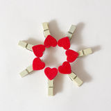 Wooden pins. With red hearts on the white background Royalty Free Stock Photos