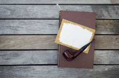 Wooden pipe and Blank old paper card on brown leather cover book Royalty Free Stock Photos