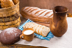 Wooden pitcher, milk and fresh bread on table Stock Photos