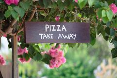 Wooden pizza take away sign board outside. Wooden sign board with text Pizza Take away outside with beautiful background of pink flowers and trees. Display Stock Photo