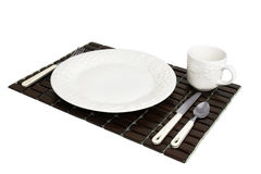 Wooden place mat with white dinner plate setting Royalty Free Stock Photography