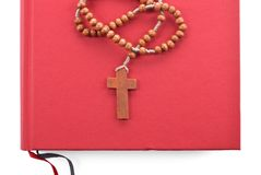 Wooden plain rosary on red book. Royalty Free Stock Images