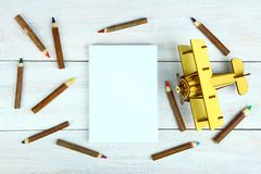 Wooden plane, sheet of paper and pencils. On a wooden background. Top view Royalty Free Stock Photography