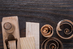 Wooden planer bricks and curled up planing chips on vintage wood Royalty Free Stock Photography