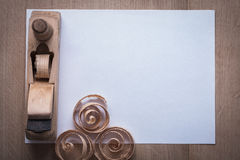 Wooden planer curled planning chips and clean sheet of paper on. Wood board copy space construction concept Stock Image