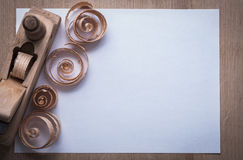 Wooden planer curled scobs and blank sheet of paper on wood boar Stock Images