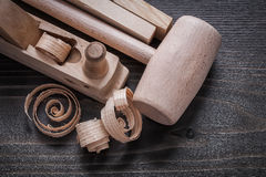 Wooden planer planks shavings and hammer on vintage wood board c Royalty Free Stock Images