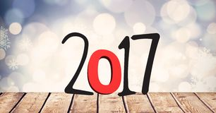 2017 on wooden plank against a composite image 3D of bokeh lights. 2017 on wooden plank against a composite image 3D of bright bokeh lights Royalty Free Stock Images