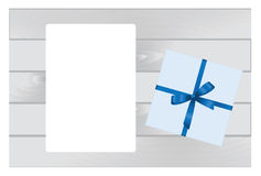 Wooden Plank Background with Blue sheet of paper and  Square Gift Box with Red   Bow. Stock Photography