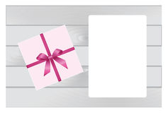 Wooden Plank Background with Pink sheet of paper and  Square Gift Box with Red   Bow. Royalty Free Stock Images