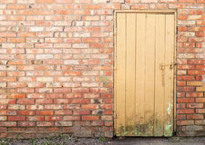 Wooden plank door, brick wall Royalty Free Stock Image