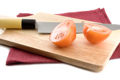 The wooden plank with a knife and tomatoes. Royalty Free Stock Photos