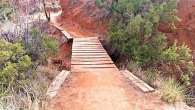 Wooden Plank Path in Red Desert. Plank bridge in hiking path with red clay and sand in desert green scrub foliage Stock Photos