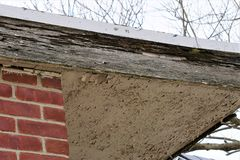 Wood timber with termite damage. Wooden plank siding of a house under the roof is damaged and compromised structurally with gaps and holes left behind by organic royalty free stock photography