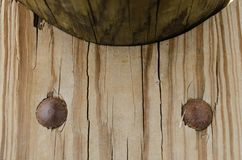 Wooden plank with two large round nails. stock photography
