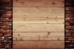Wooden plank on a wall of bricks Stock Images