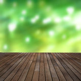 Wooden planking. Brown stained grainy wooden planking or decking with soft green background Stock Images