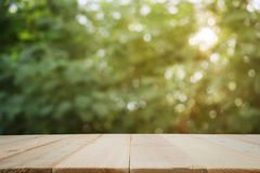 Wooden planks with blur image of light streaming through leaves. Royalty Free Stock Photography