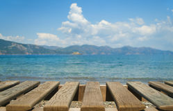Wooden planks at foreground with sea and mountains at background Stock Photo