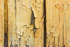 Wooden planks fragment with yellow peeled paint, abstract texture.  royalty free stock photo